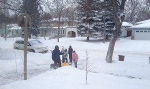 Grandad and Dad teaching the kids how to shovel.