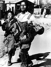 The young boy being carried was one of the confirmed dead.  His sister runs beside...